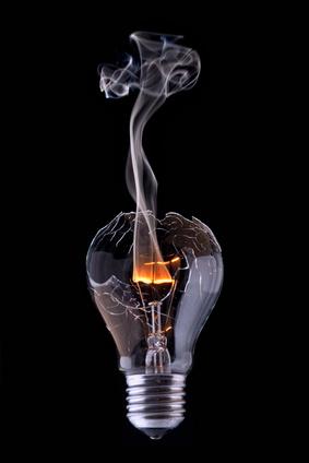 Foto einer geplatzen Glühbirne mit noch glühenden Draht, Rauch aufsteigend