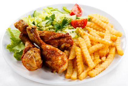 Foto mit Hähnchenschlegel, Pommes und Salat auf weißem Teller