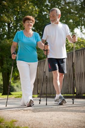 Foto mit Frau und Mann mit Walkingstöcken laufend