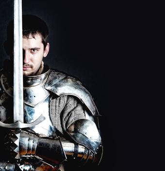 Foto von Mann in Ritterrüstung mit Schwert senkrecht nach oben haltend