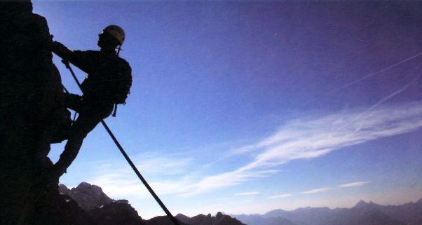 Foto vom Bergsteiger am Fels im Gegenlicht